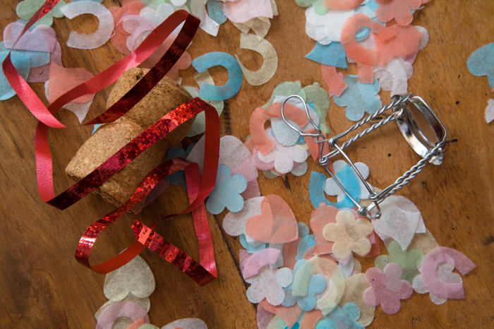 Confetti and Champagne cork on wooden floor